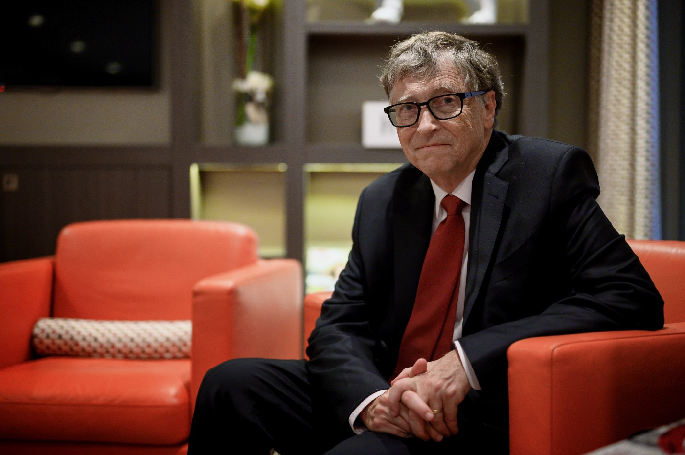 Bill Gates sits on a red armchair and poses for a picture during the funding conference for the Global Fund to Fight AIDS.