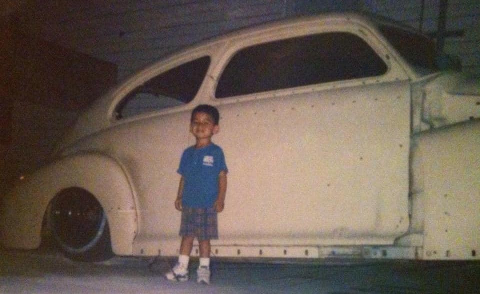Small child standing in front of a classic car from the early 1940's