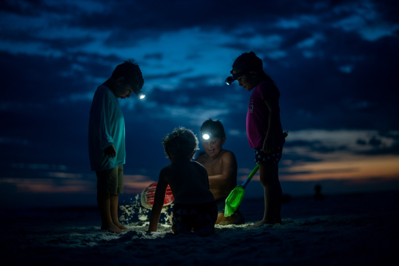 Four young boys wearing head lamps as they play on the beach with sand toys after the son has gone down.