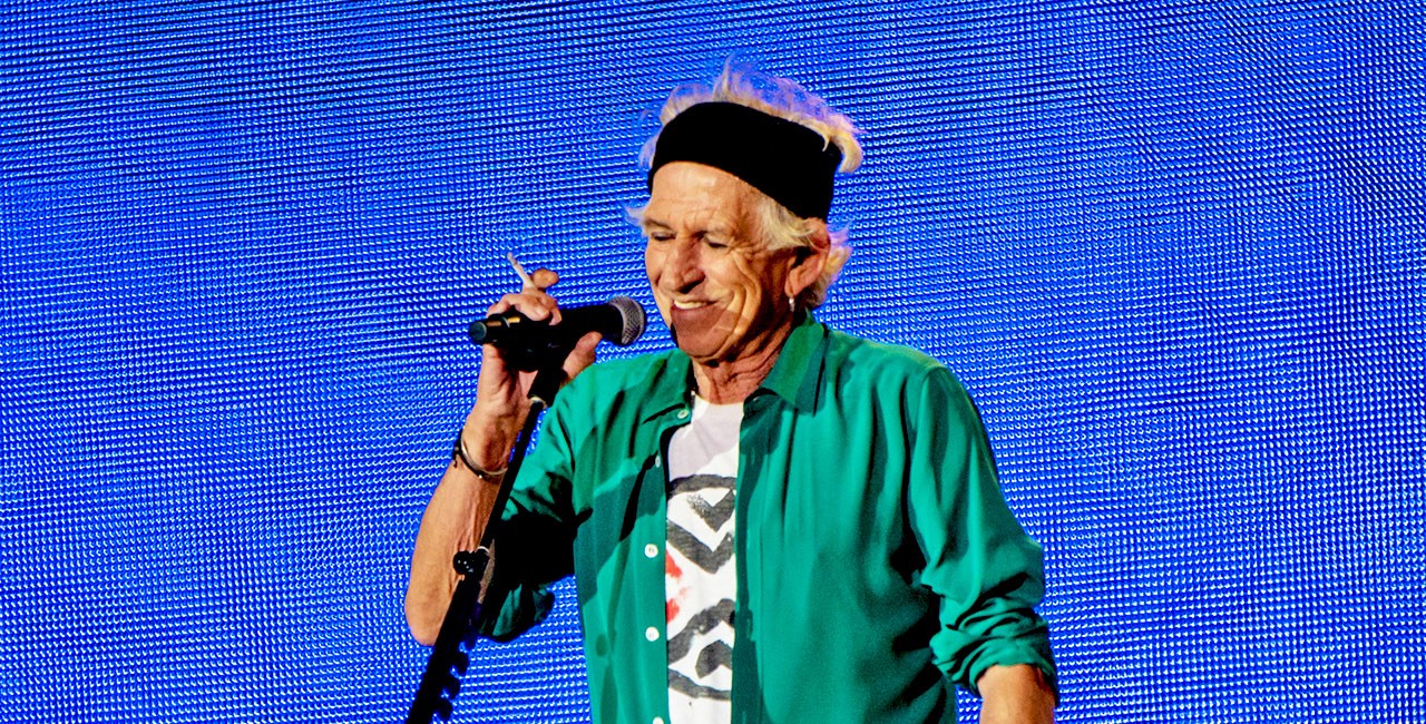 Keith Richards in a green shirt and black headband holding a microphone (and a cigarette) in front of a blue lightboard