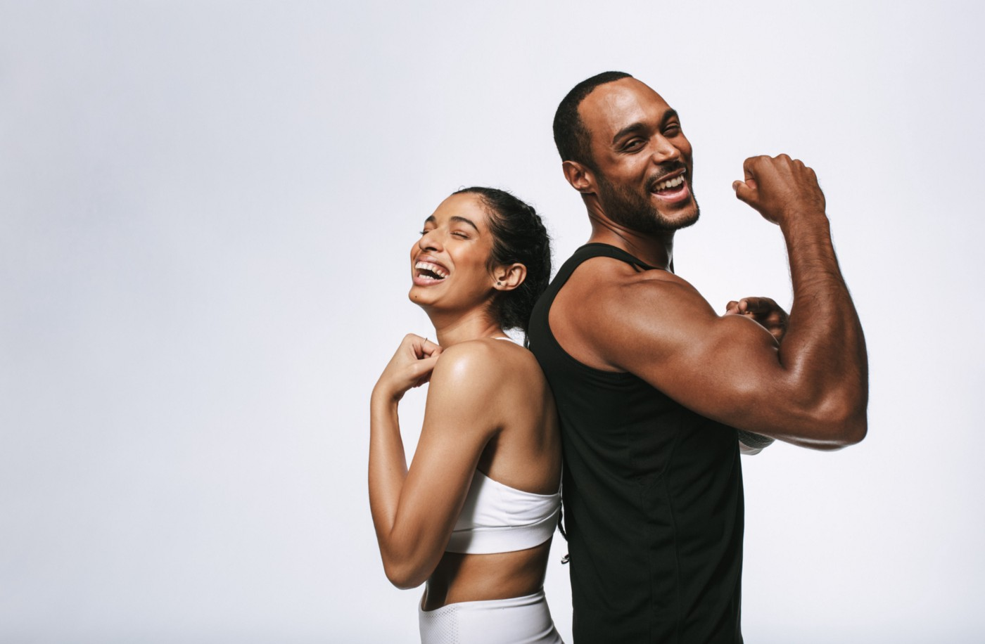 Happy fit couple showing off their muscles.