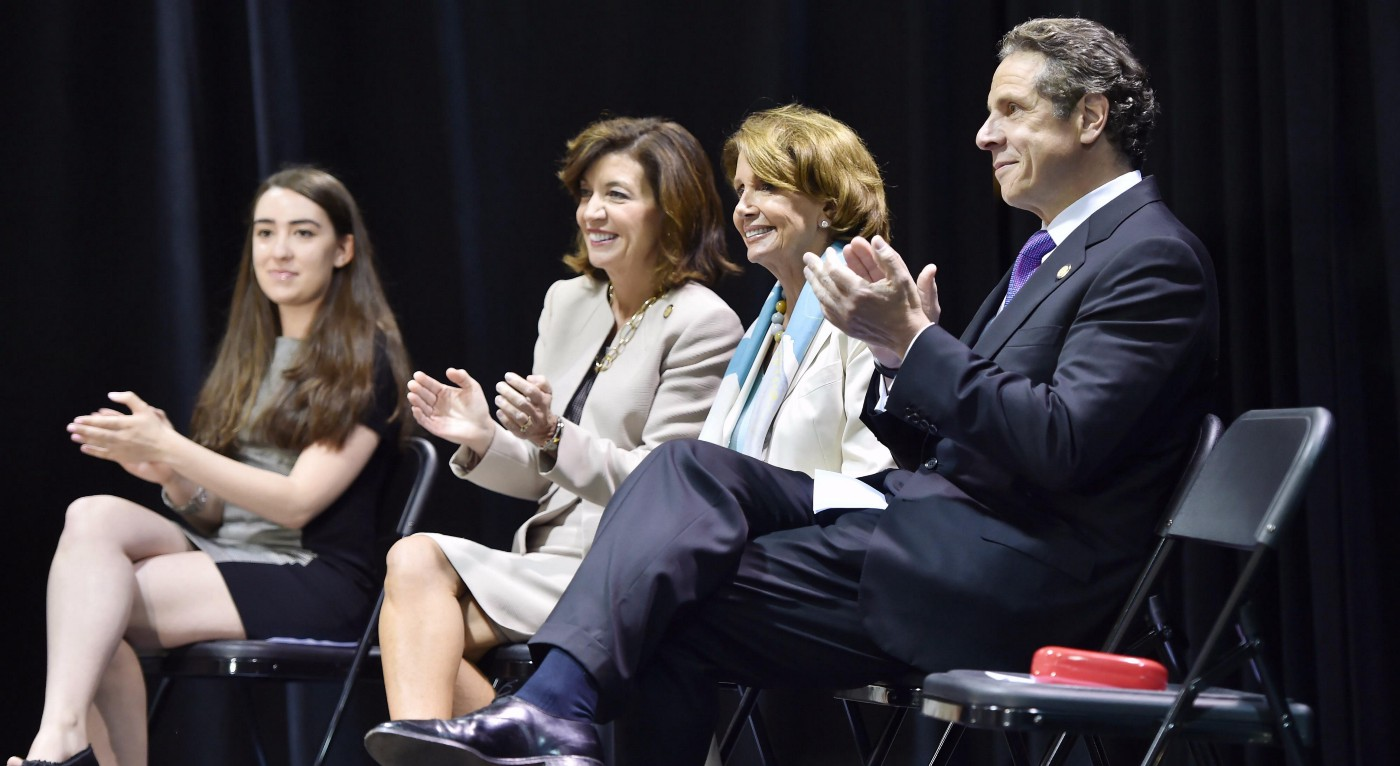 2015 panel with Governor Cuomo, Nancy Pelosi, Lt. Gov. Kathy Hochul, and presumably an aide to the governor's office on a stage with folding chairs and black curtain