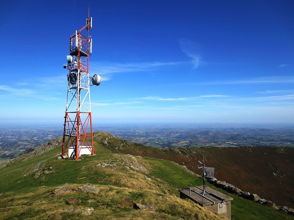 The image shows an antenna at the summit of Baigura with Labourd in the French Basque Country in the background.