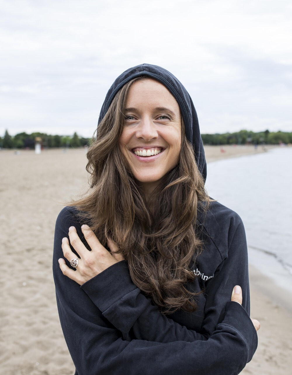 Photo of the interview subject, Jo-Anne McArthur, smiling widely on a beach, wearing a navy hoodie