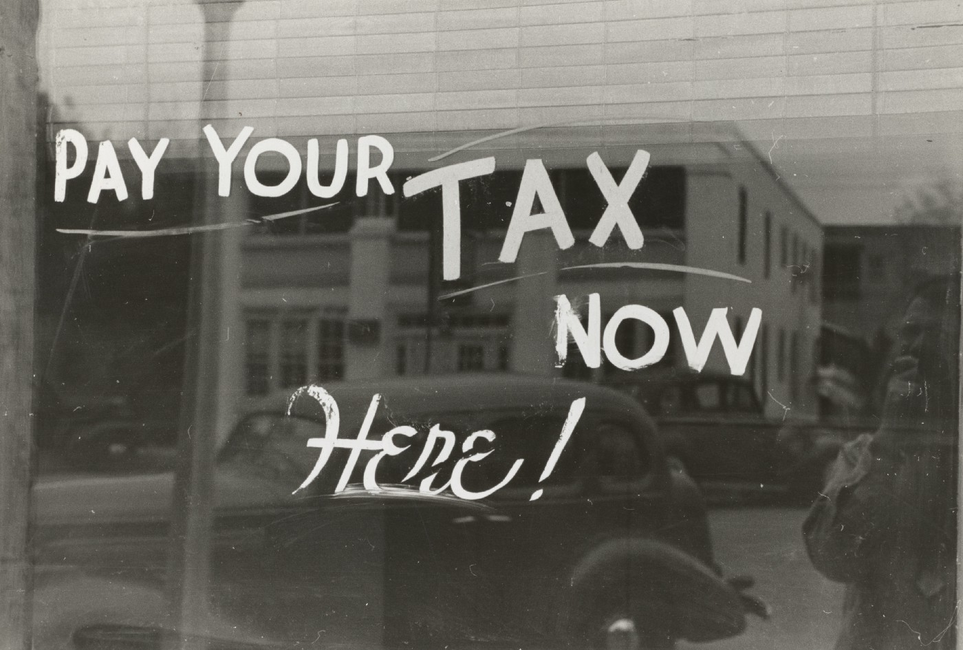 Words: Pay your tax now here written on a window