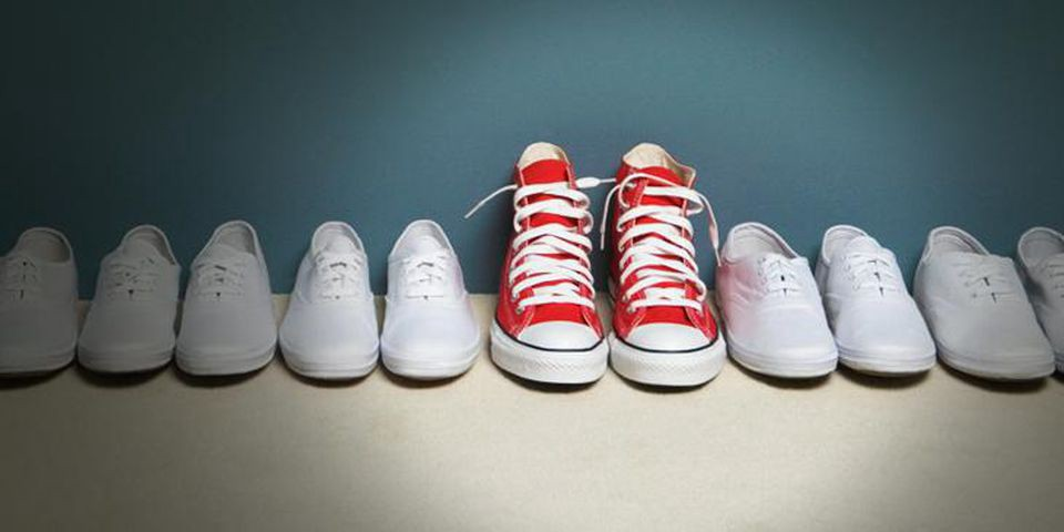 Pairs of white tennis shoes in a row, with a pair of bright red high tops standing out in the middle.