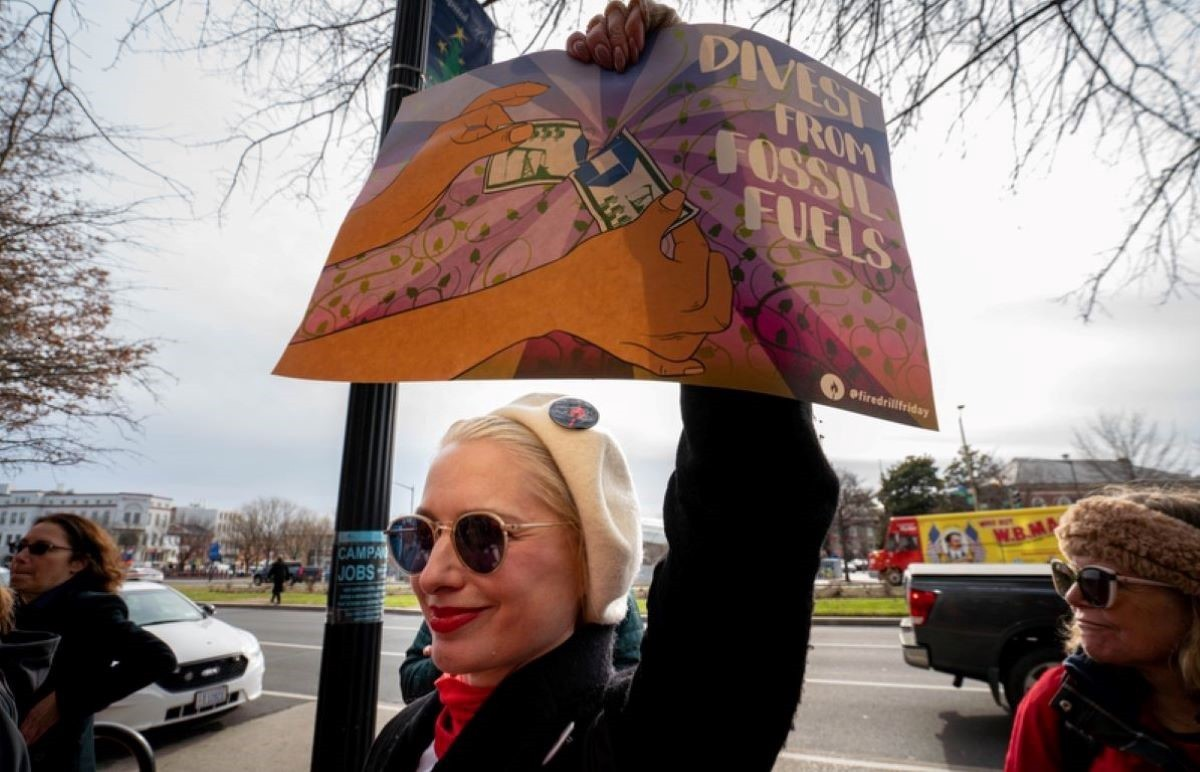 """A woman holds up a sign that reads, """"Divest from Fossil Fuels."""""""