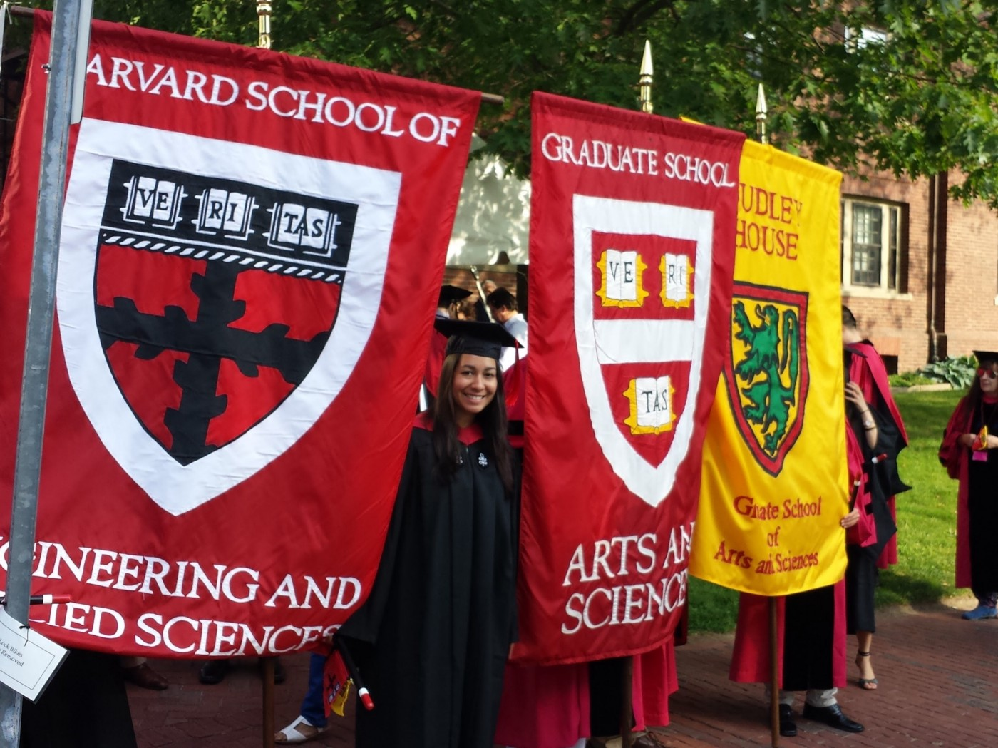 Author posing by Harvard school flags during commencement