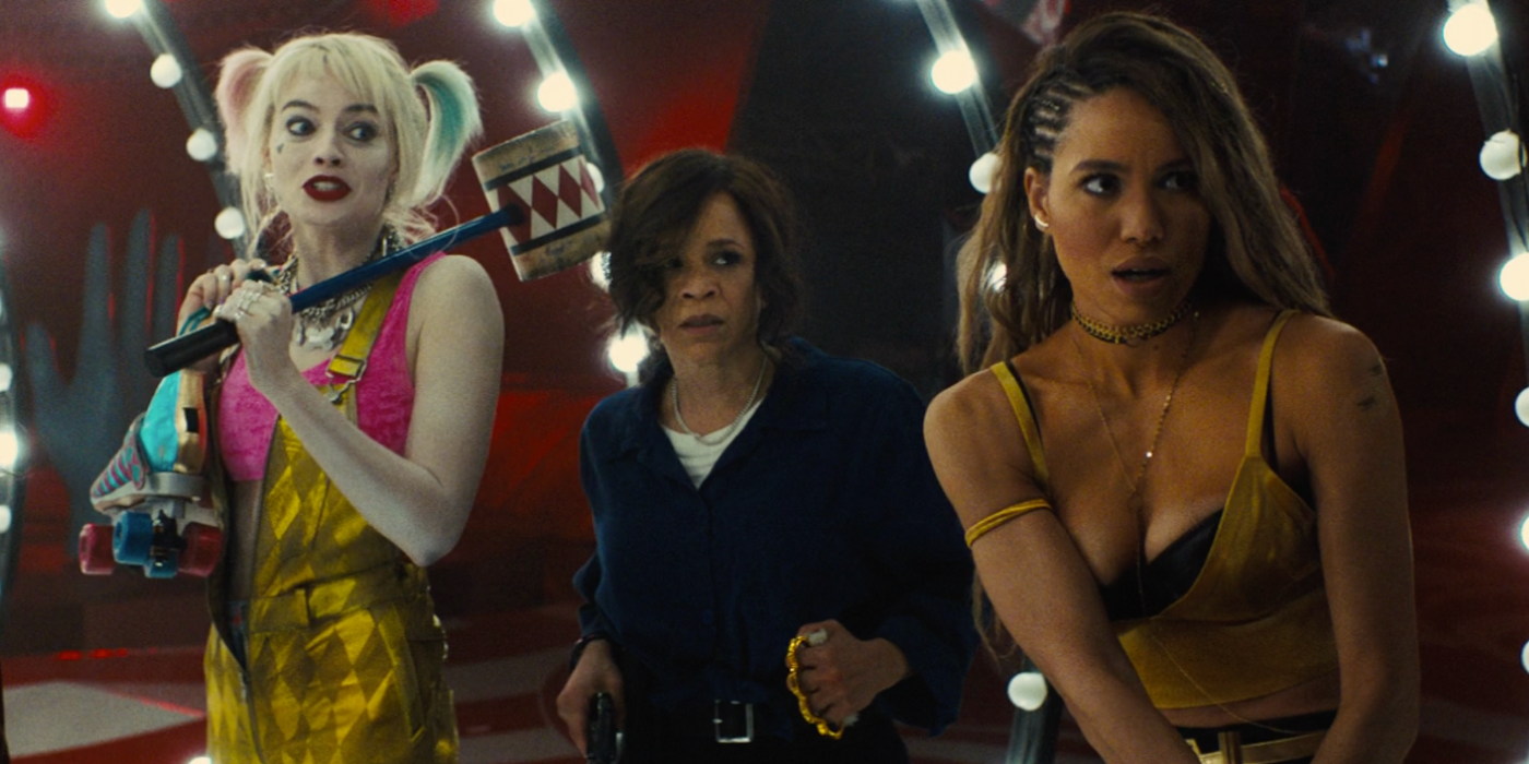 (from left to right) Robbie, Perez, and Smollet-Bell, preparing for a clash with henchmen, with circus lights behind them.