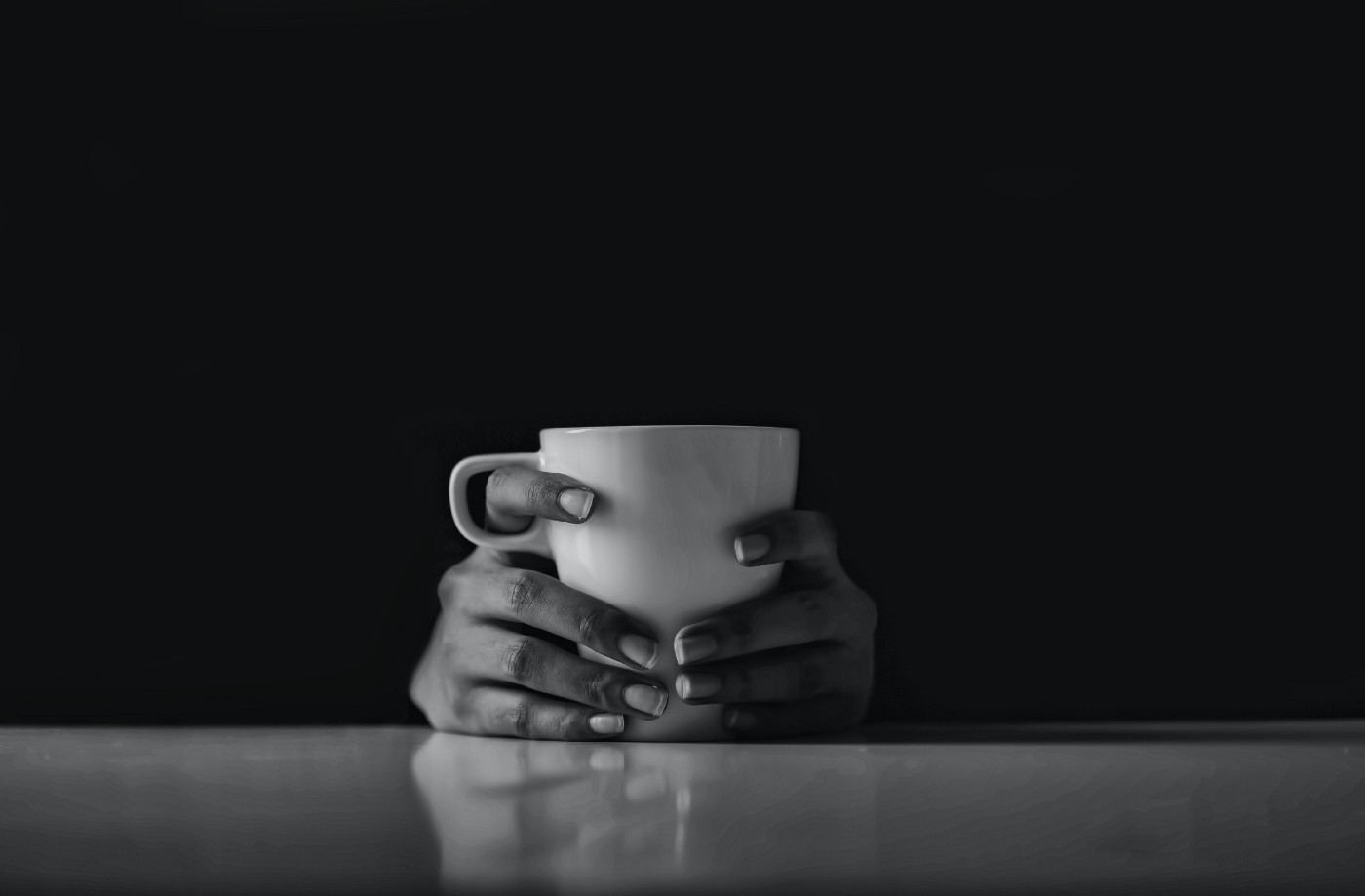 Two hands holding a coffee mug against a black background