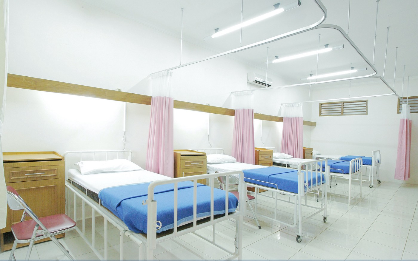 Three hospital beds sit in a row surrounded by bright lights and white wallpaper.