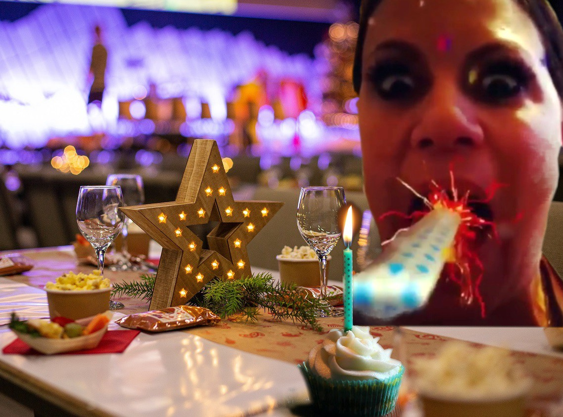 Silly photo of me blowing a paper party favor noise maker, those things that unwind from your mouth, out to a candle in a birthday cupcake, all set atop a lavishly decorated birhtday table with city lights in the background.