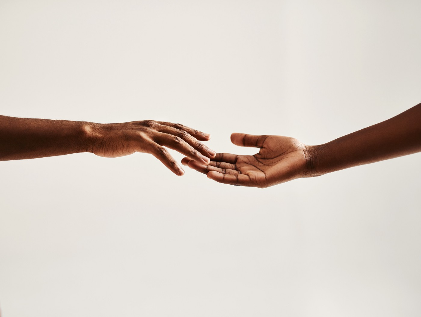 A photo of two hands touching each other.