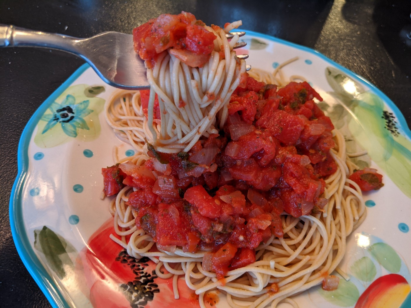 A plate of plant-based spaghetti sauce served over spaghetti noodles.