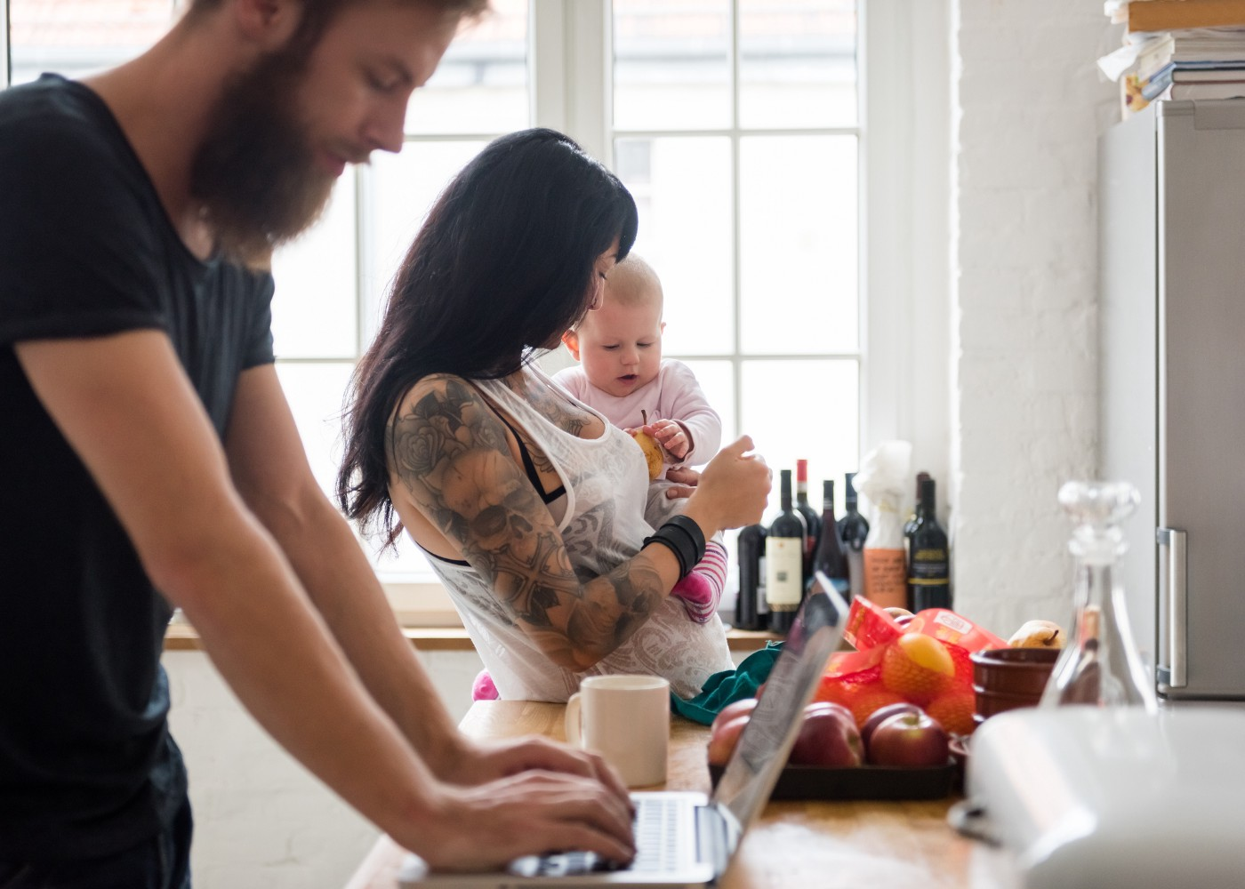 Young mother holding her newborn baby in the kitchen while the father works on his laptop in the foreground.