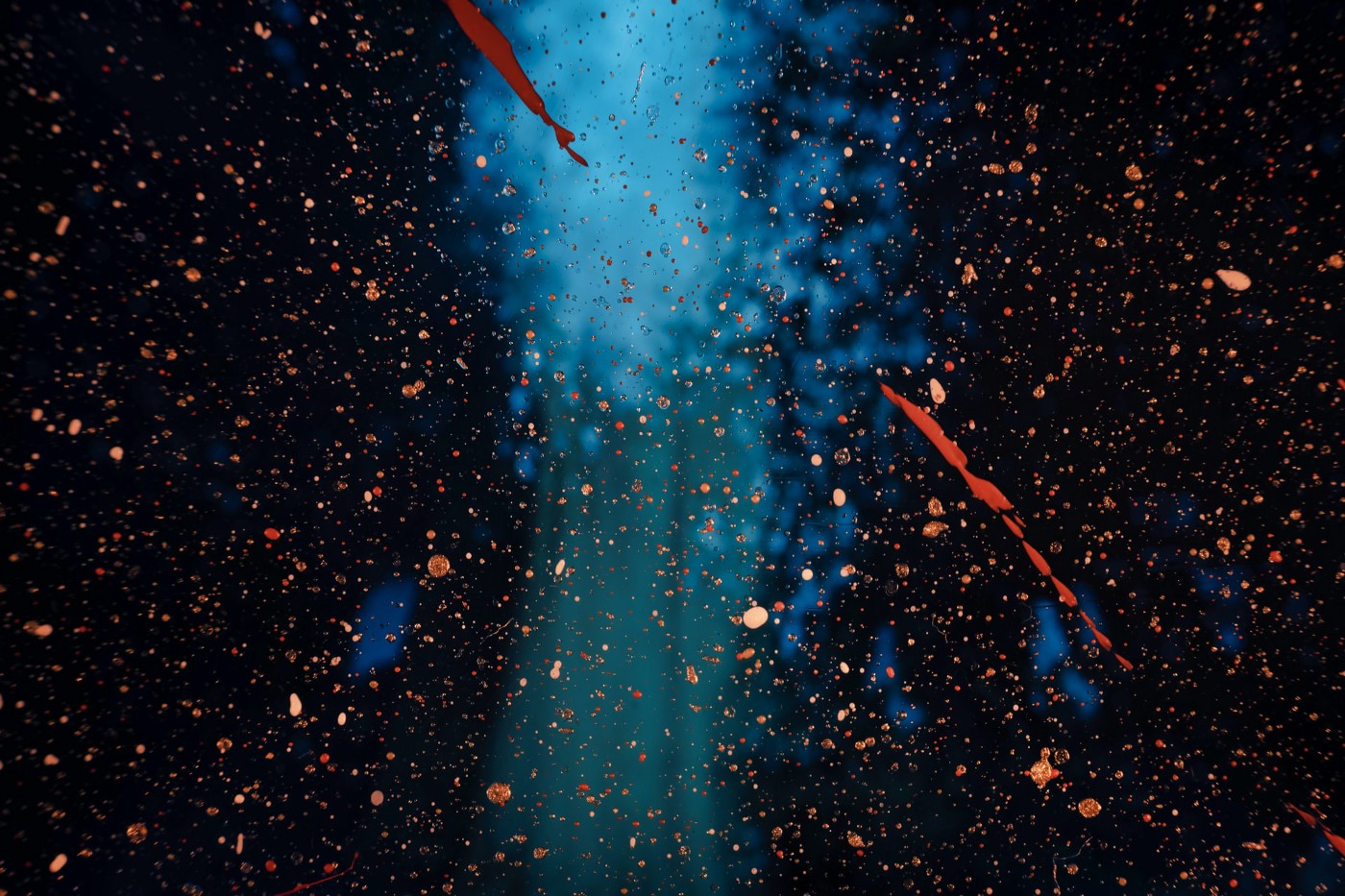 An explosion of red particles hover on a blue column on a black background.