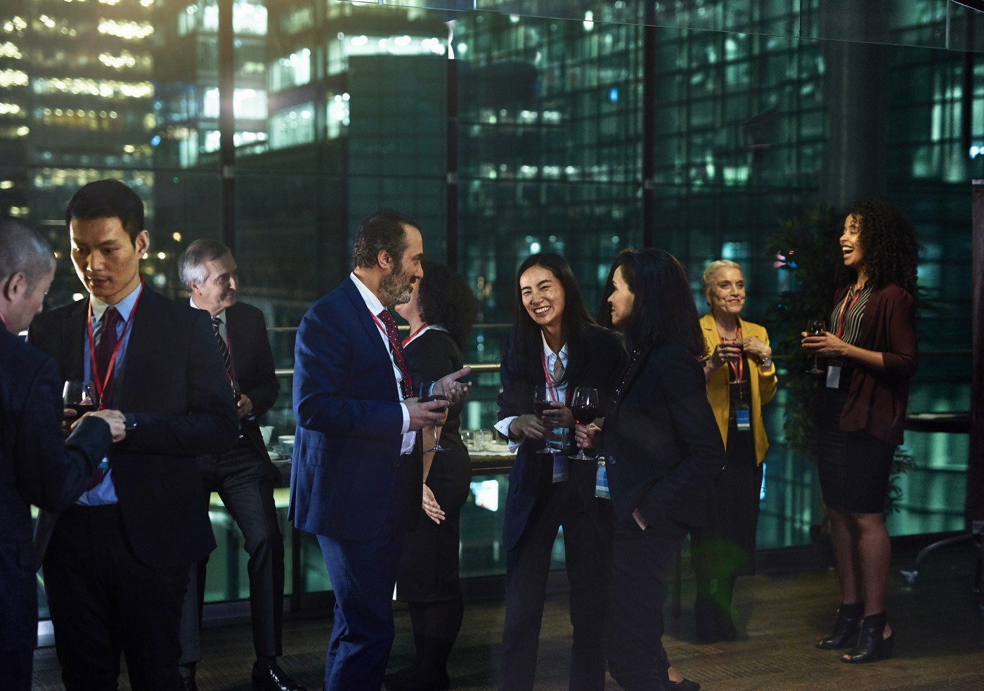 A photo of business people networking in an office building with glass windows at night.