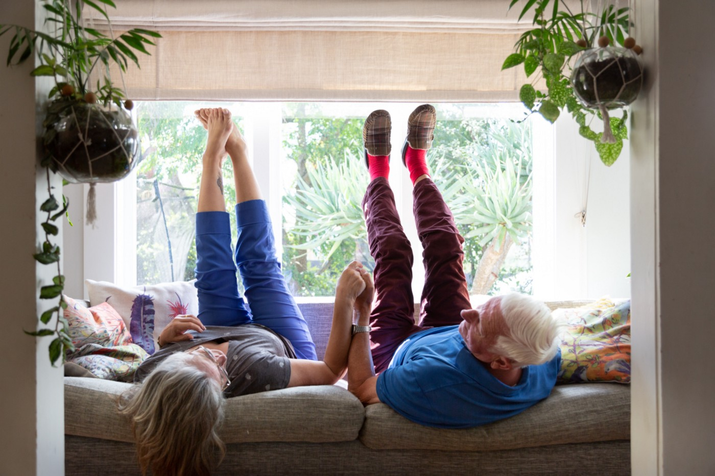 A senior couple lie next to each other on the sofa with their legs in the air. They are holding hands.