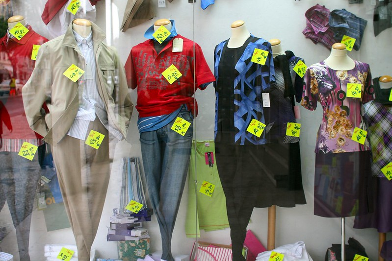 A department store window display of several headless mannequins wearing clothes that are covered in neon yellow price tags that look like post-it notes