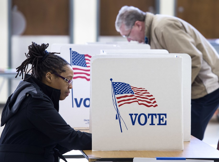 A black woman in a black coat with braids pulled back in a bun sits at a table with a cubicle decorated with vote and a flag