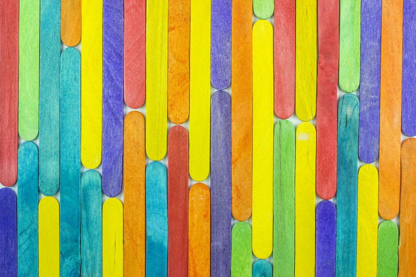 A photo of colorful popsicle sticks lined up to look like a wallpaper.