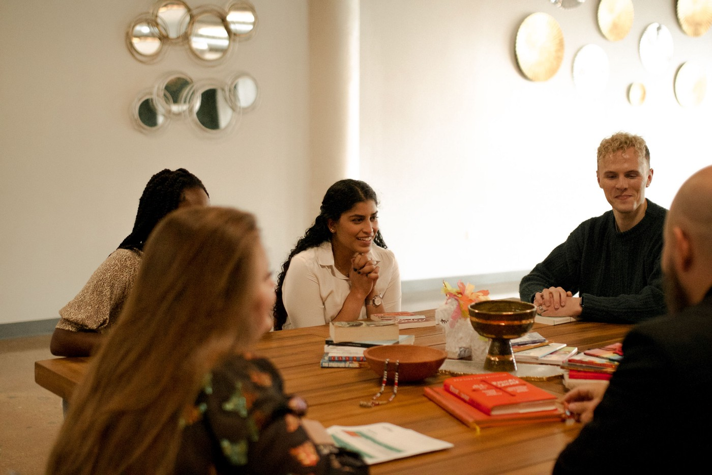 A group of five employees sit around a wooden meeting table talking, smiling, and laughing.