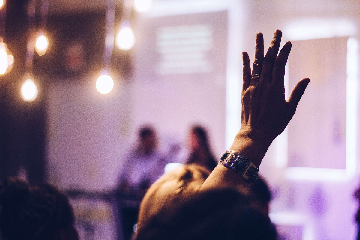 Symbolic image: Someone is rasing their hand during a presentation.