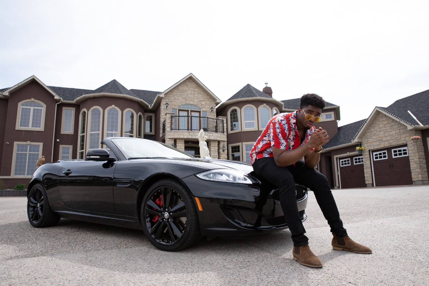 Man posing on car in front of mansion