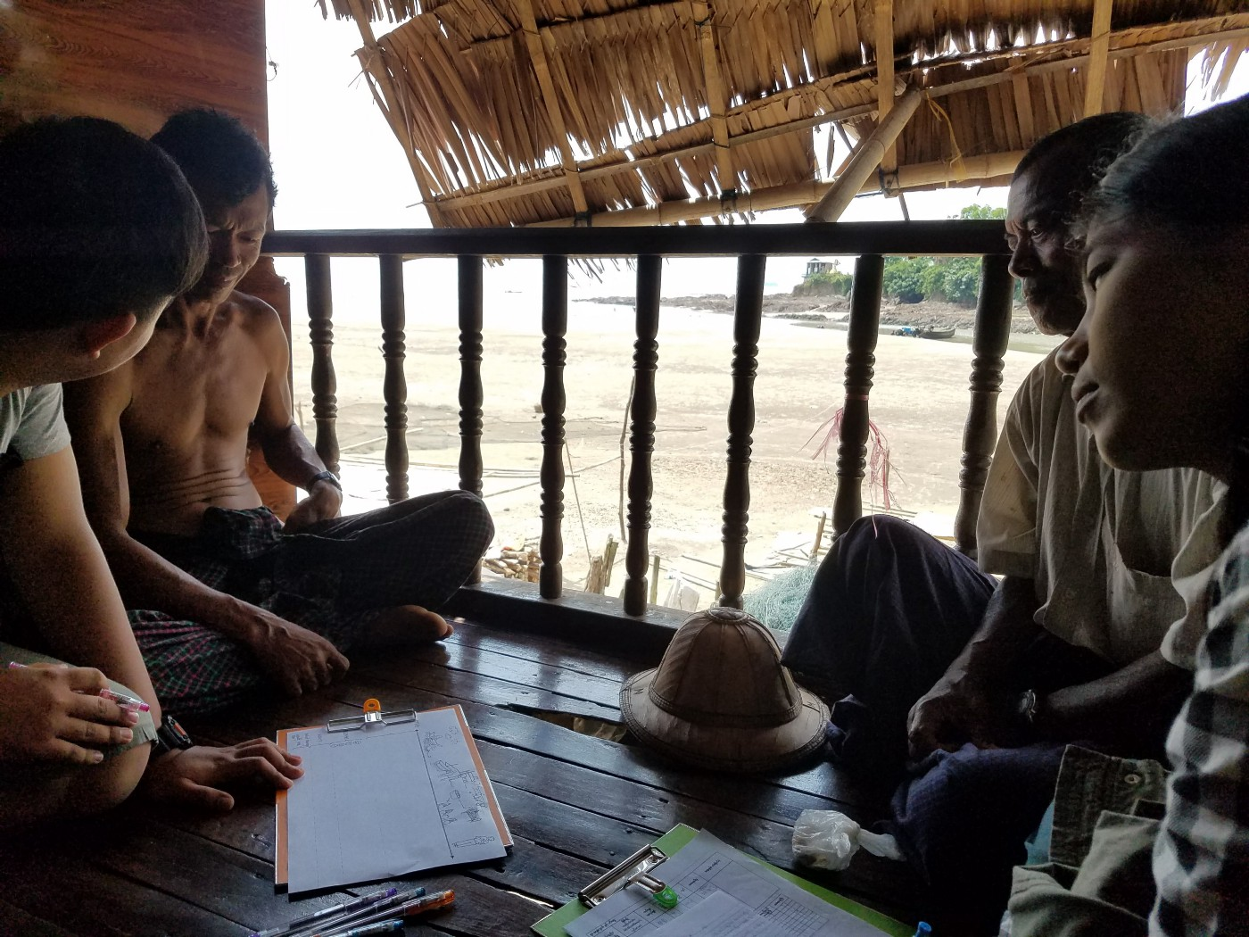A group of people sit on a small porch overlooking a beach. One young researcher is interviewing two fishers, with another student looking on.
