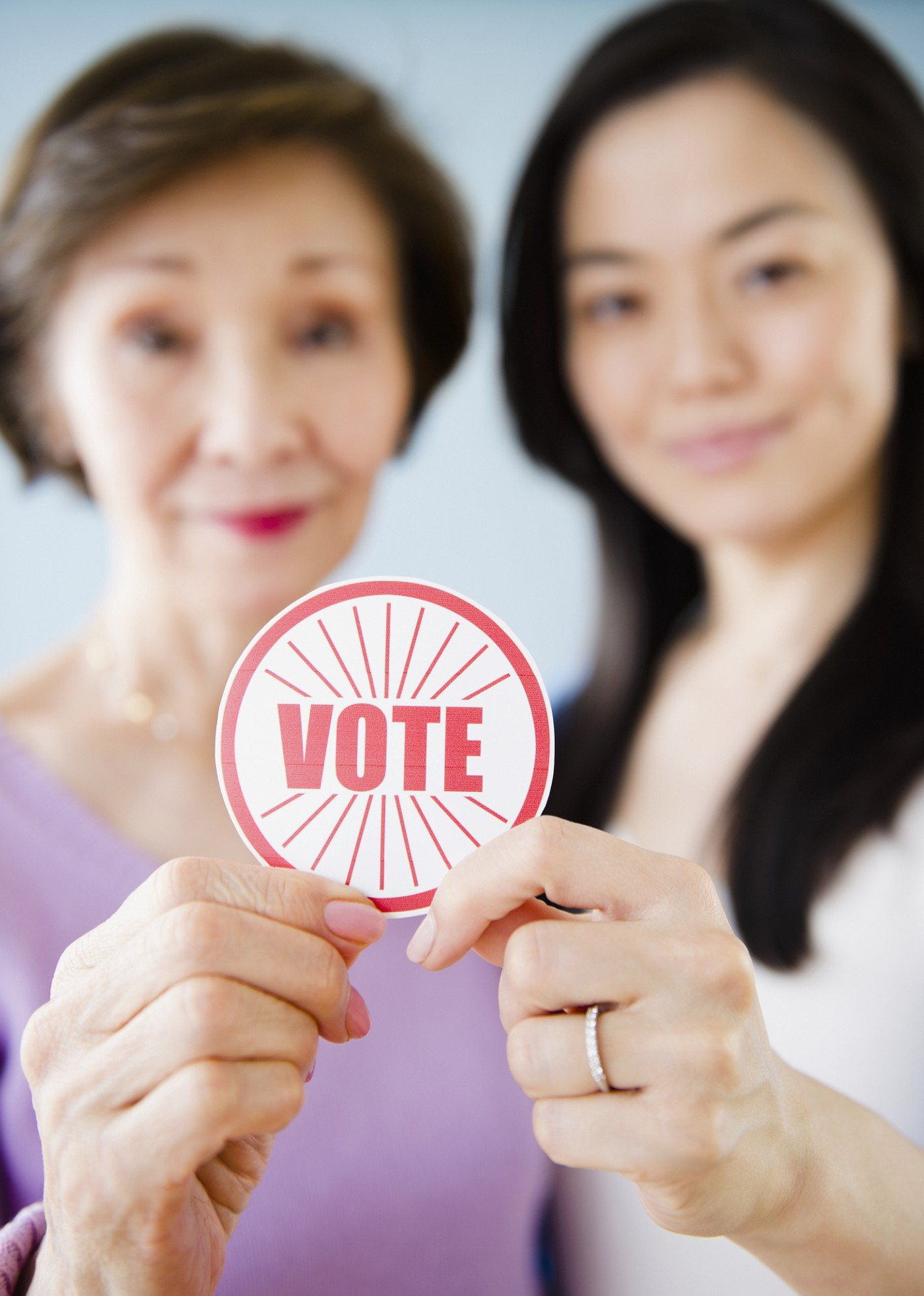 Asian mother and daughter holding a VOTE sticker.