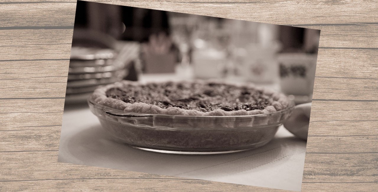Black and white photo of a pecan pie in a glass baking dish on a kitchen counter against a woodgrain background
