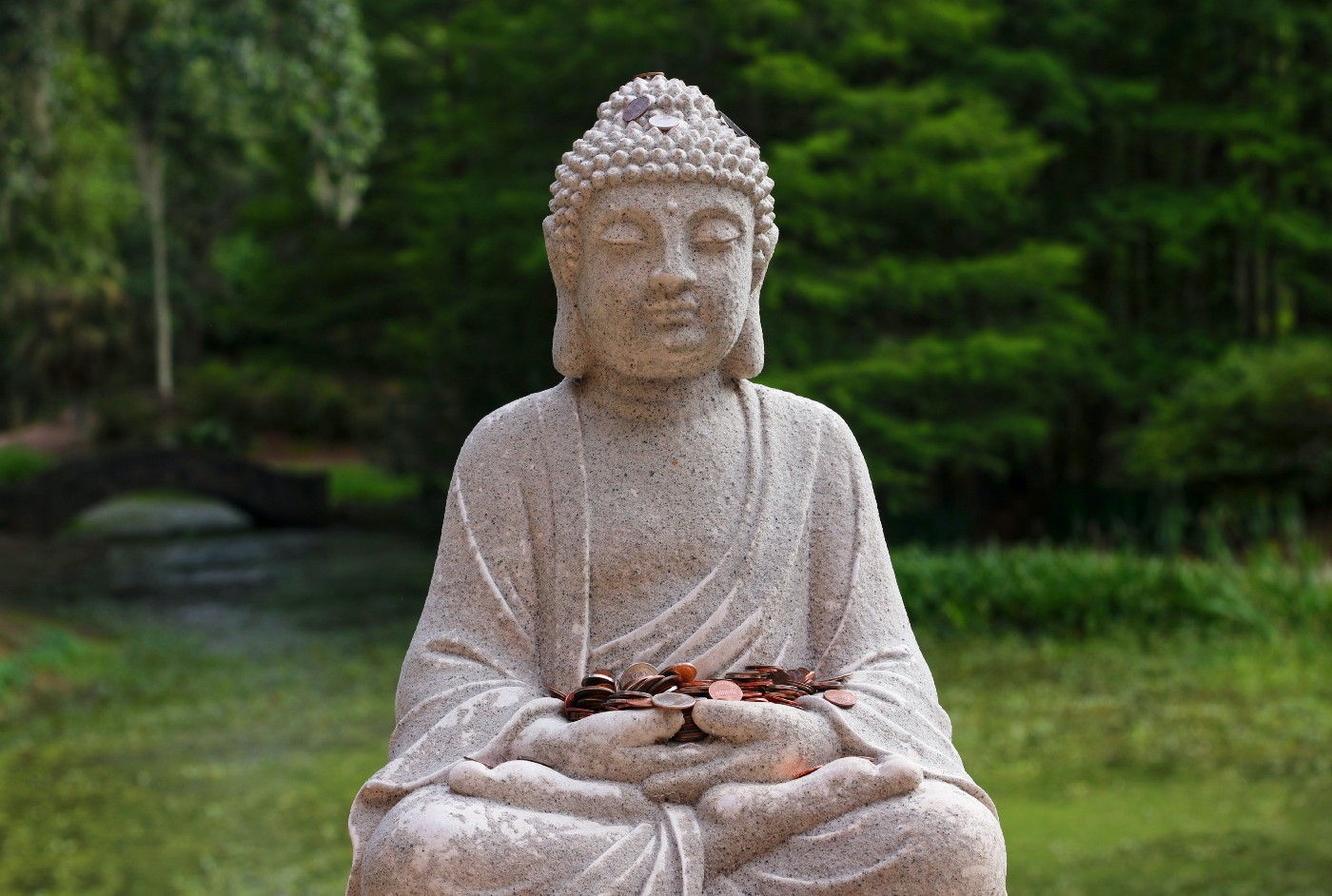 A statue of the Buddha holding coins, legs crossed.