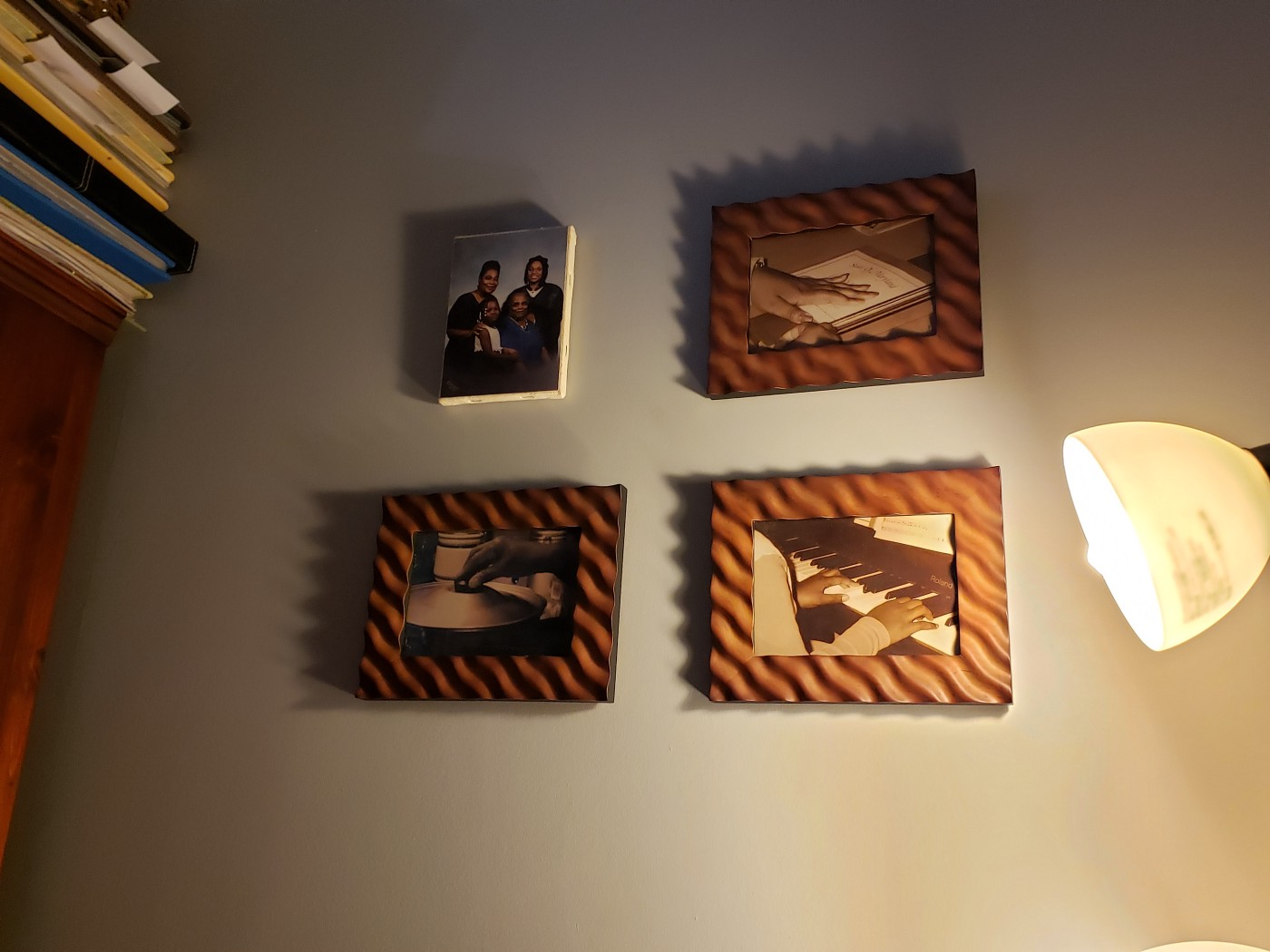 Family portraits hanging on the wall with dim lighting.