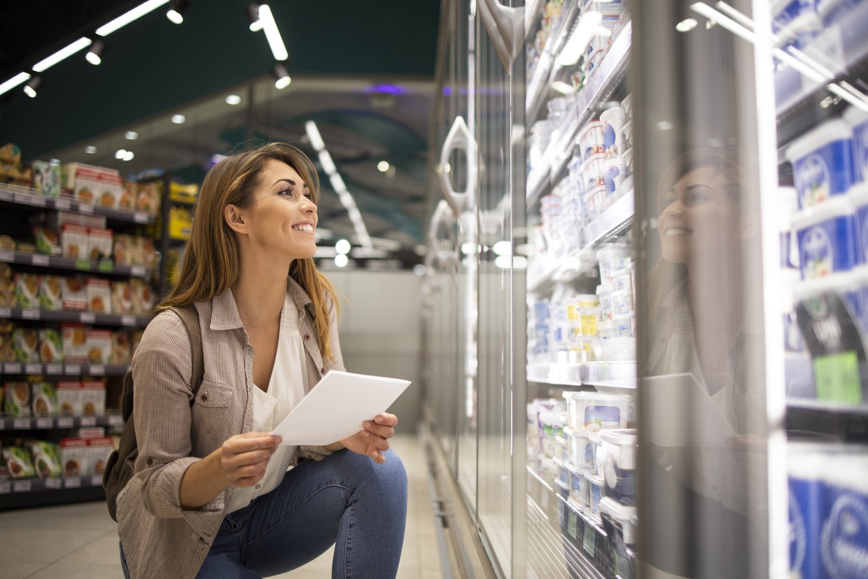 Beautiful woman with shopping list buying food in supermarket.