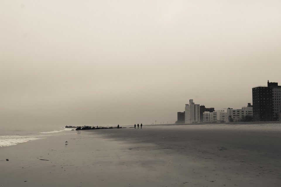 Moody photo of the ocean on the left & apartment buildings on the right, separated by a strip of sandy beach at Coney Island.