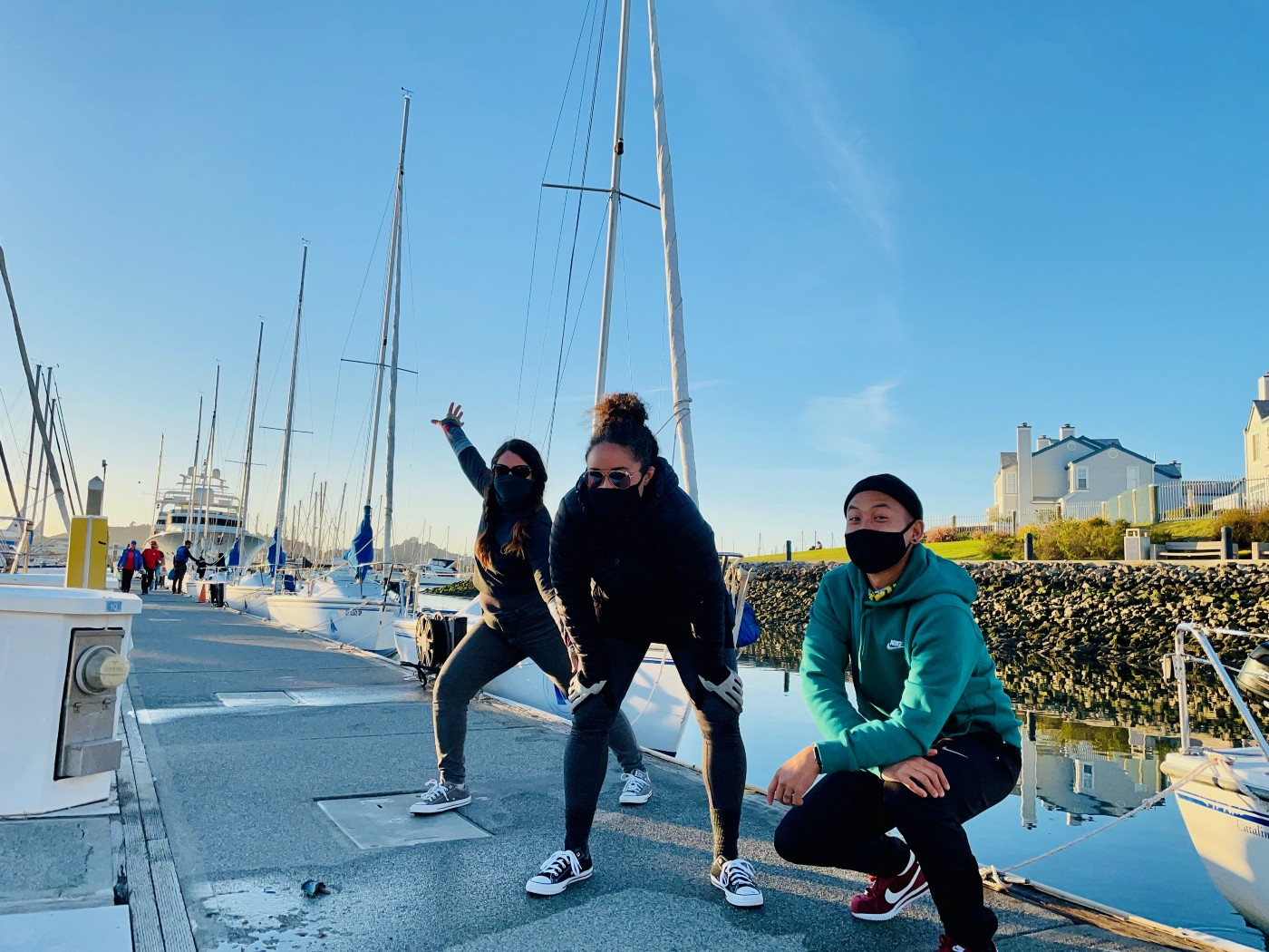 Image of three friends: Jessa takes a power stance with one arm open wide the other reaching down, Mariah crouches with her hands on her knees, and Geoff squats closer to the ground with his arms crossed and resting on his knees. The pose in front of their first keel boat.