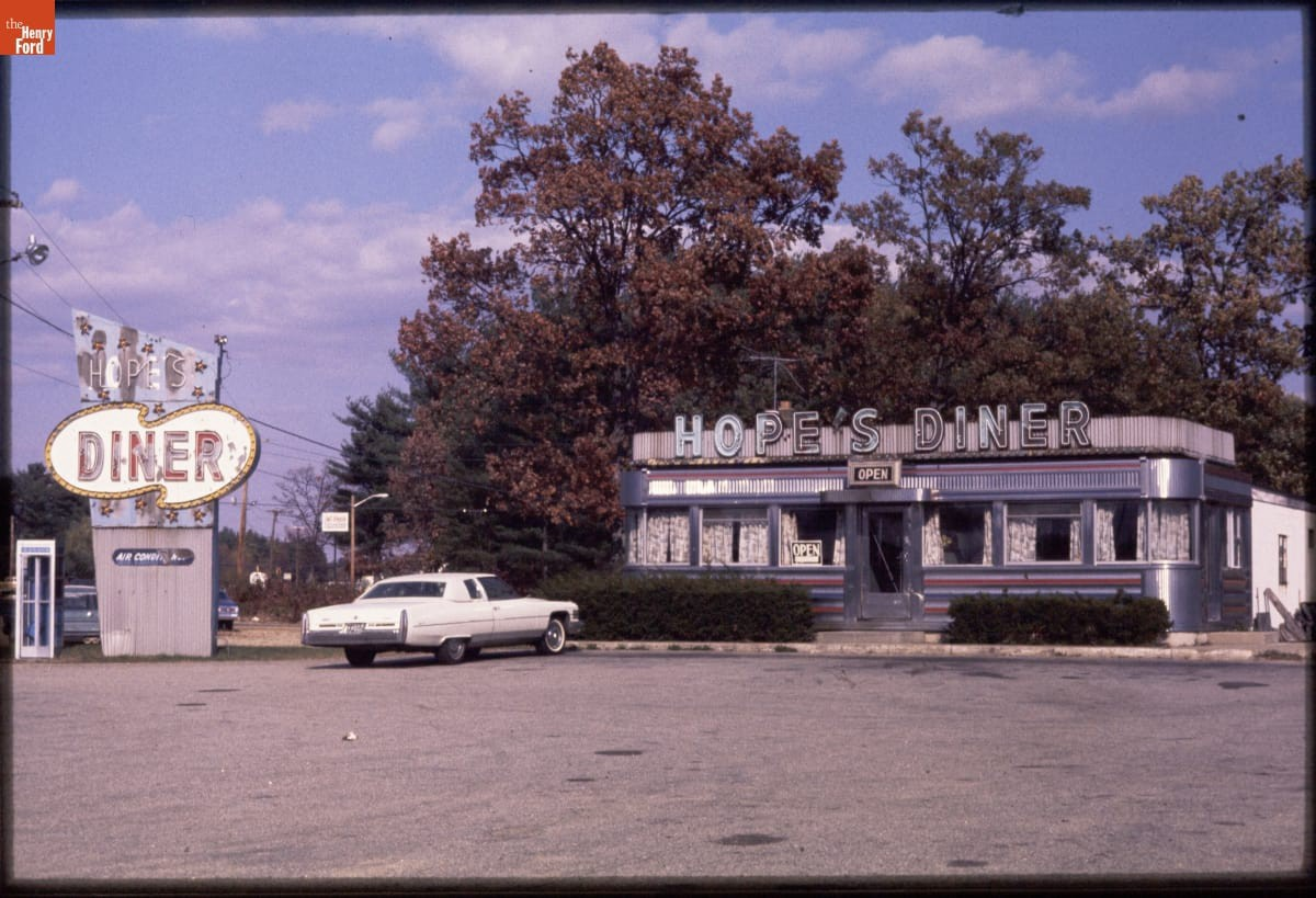"Small building at right with silver letters spelling ""Hope's Diner""; sign with same words to left. White car parked in front."