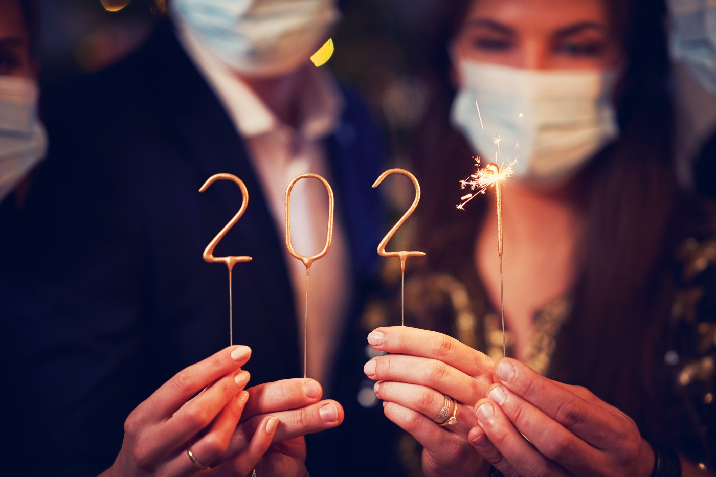 Two people in masks holding 2021 candles and a sparkler.