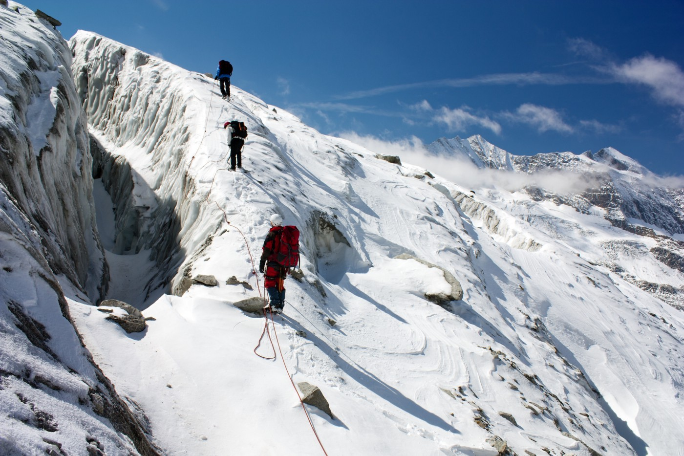 Hikers climbing up snowy mountain