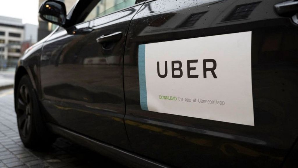 An Uber car with the company logo attached.
