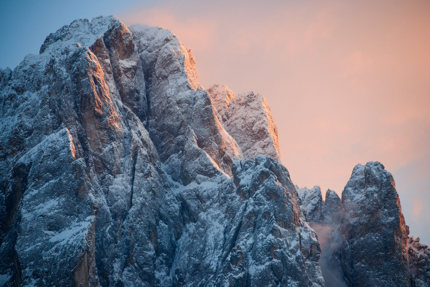 a snowy mountain peak against a background of a rosy sky