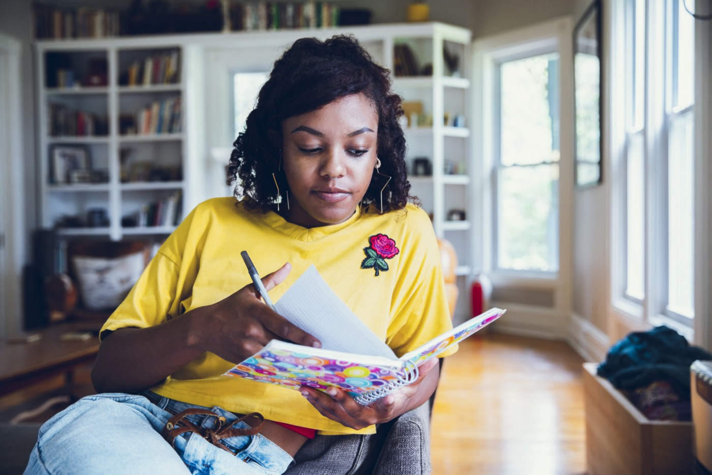 Young Black woman writing in her journal.
