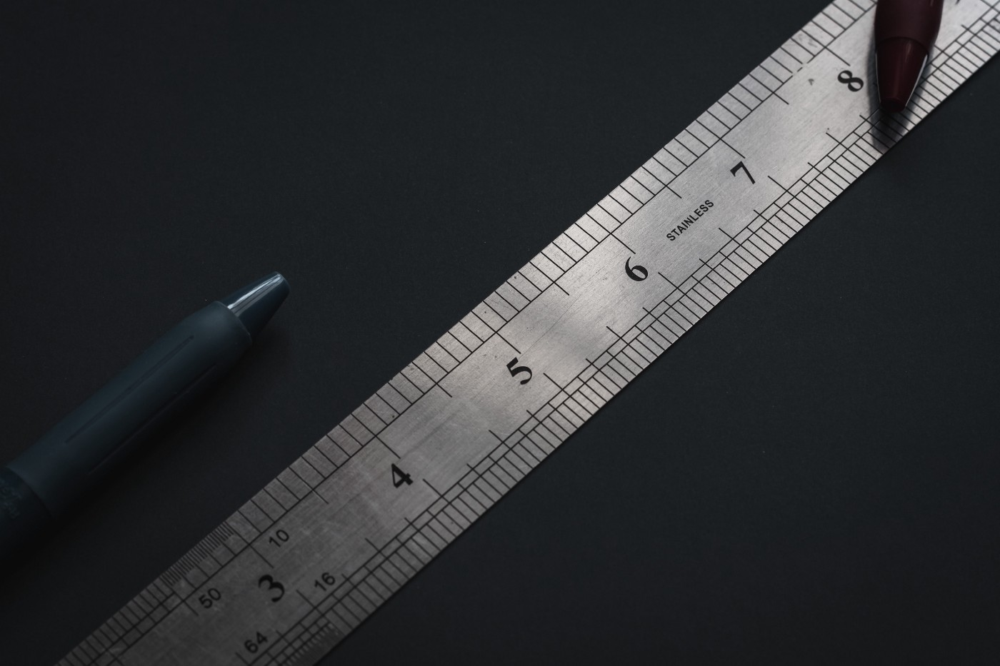 A metal ruler and two pens against a black background.