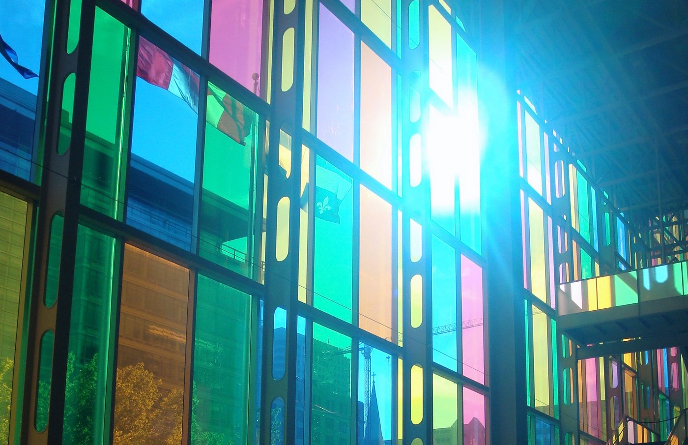Multicolour stained glass with light shining through and Canadian flag on opposite side (photo by Kate Kalcevich)