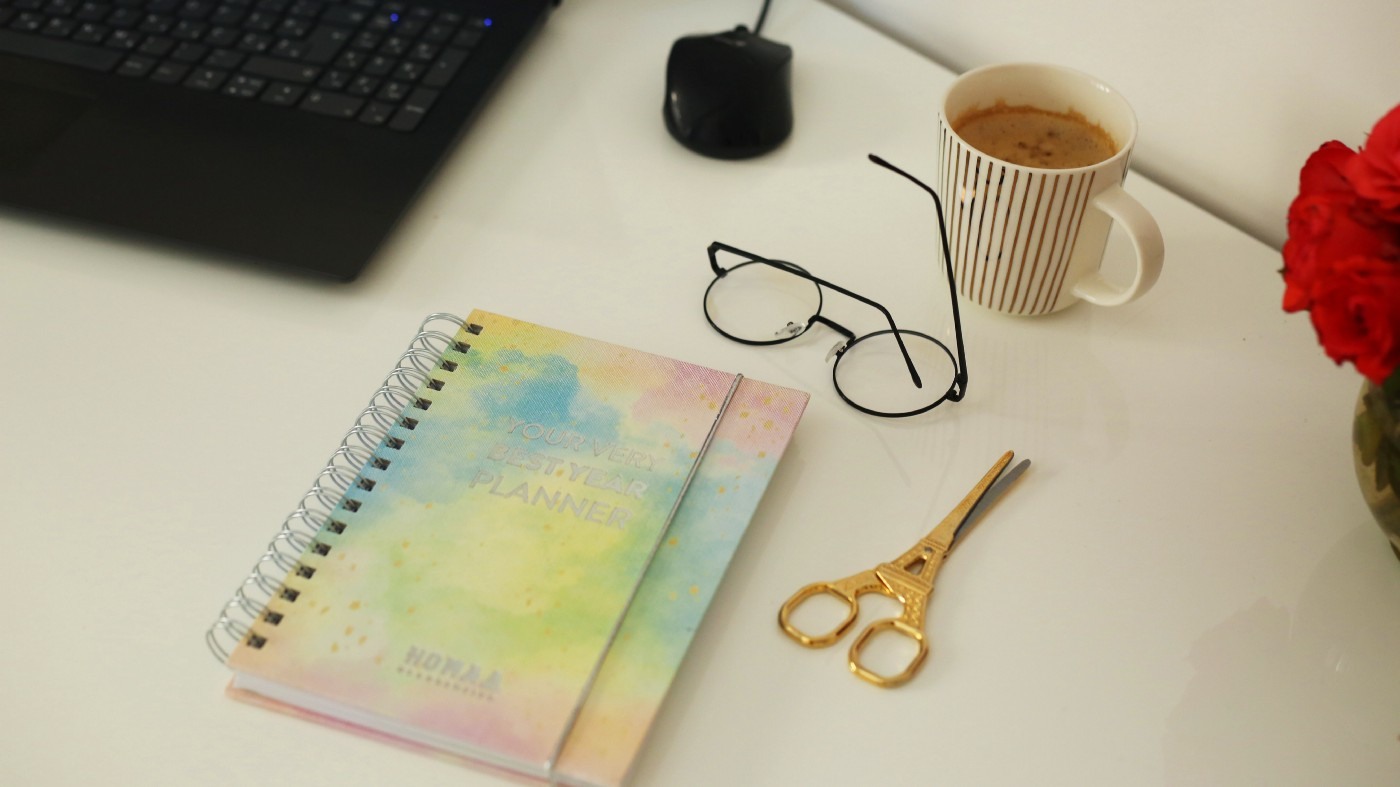 Photo of a computer keyboard and mouse, spiral bound journal, scissors, glasses, cup of coffee.