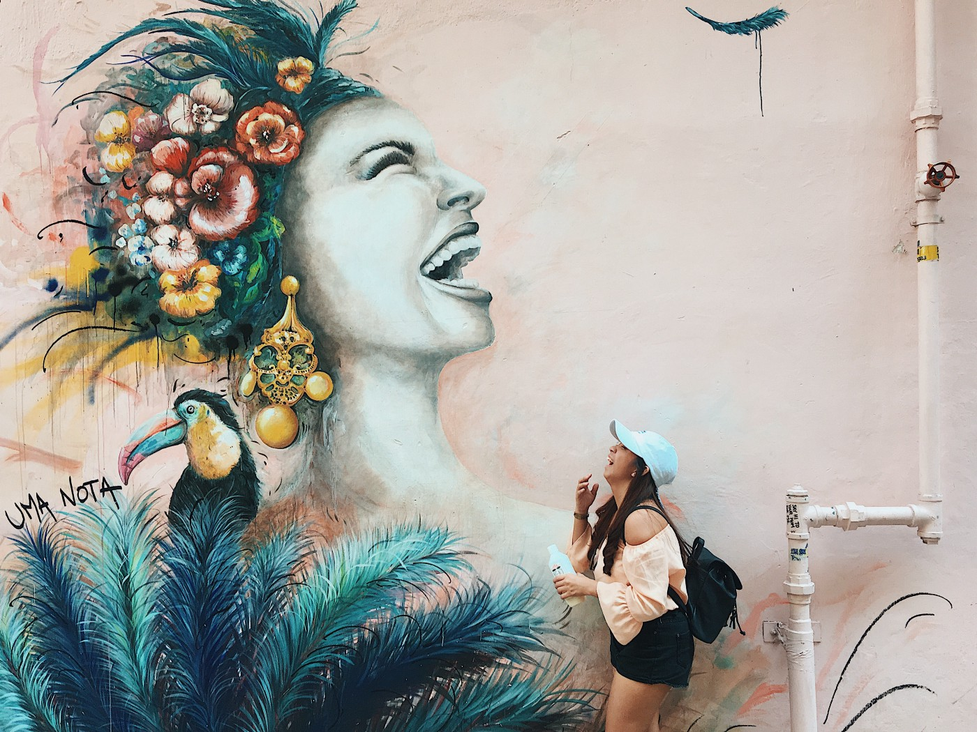 Woman laughing at a large mural of another woman laughing.