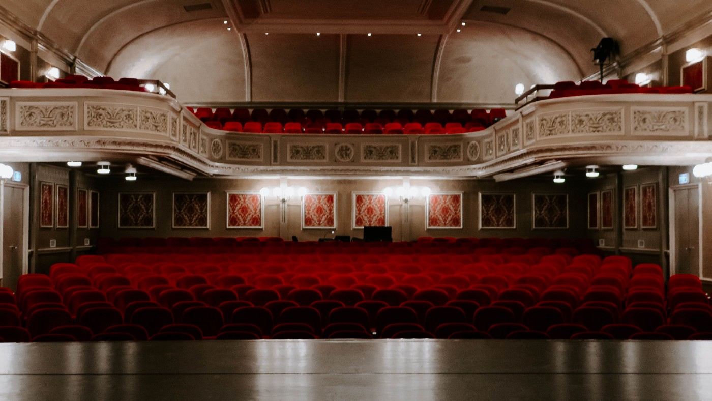 The view from the stage of an auditorium, looking out at red seats and ornate walls.