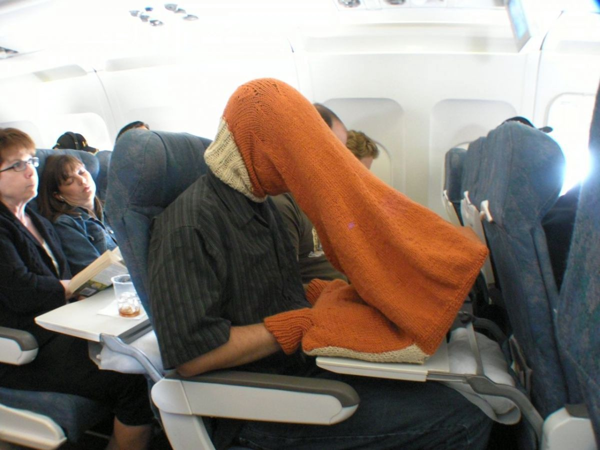 2016 image of person on plane typing into laptop wearing a knitted garment that obscures the screen and their hands