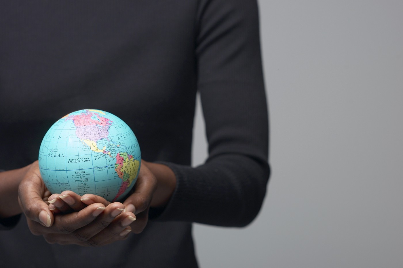 A woman holding a globe in her hands.