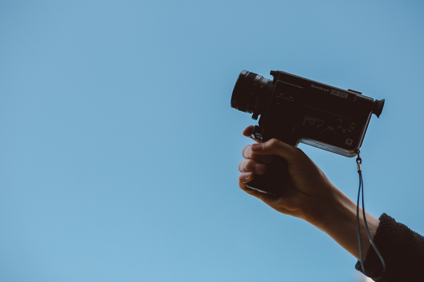 Person holding a video camera against a blue background